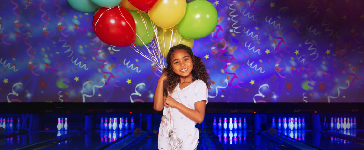 little girl in a bowling alley holding balloons