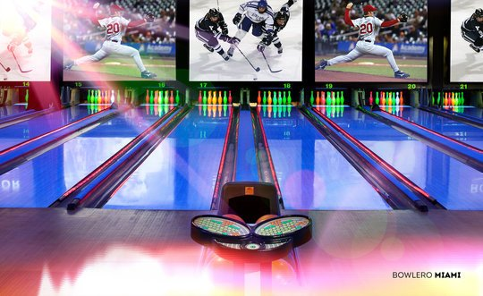 Blacklight Bowling lanes with sports on the screen