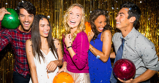 Group of 5 young adults with bowling balls, smiling in front of a glitter background