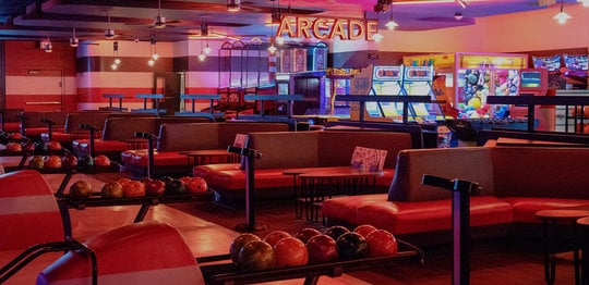 Bowling alley lanes and seating area with an arcade visible in the back