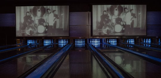 Bowling lanes with pins and music videos above