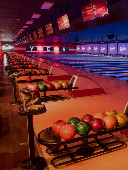 Ball returns and bowling lanes with 'YES' written on the wall