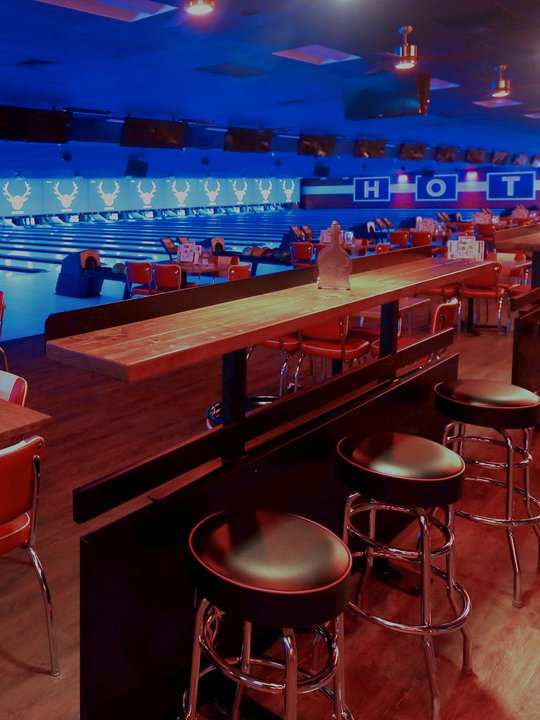 view of bowling lanes lit blue from the seating area
