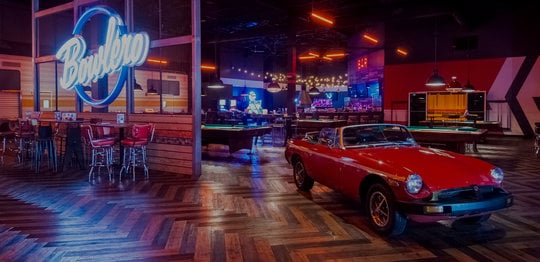 Retro red car with red billiards tables behind it