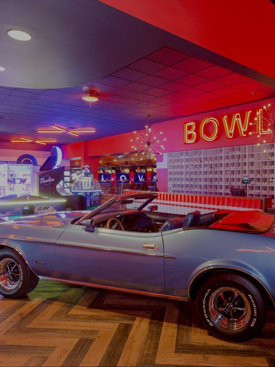 Blue vintage car inside a bowling alley with an arcade in the background