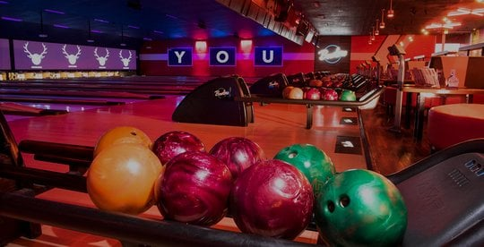 closeup of bowling balls and view of lanes