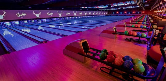 Ball returns and bowling lanes with 'LUST' written on the wall