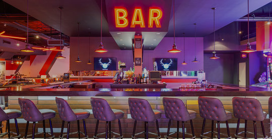 bar stools, a bar, and an orange neon 'bar' sign
