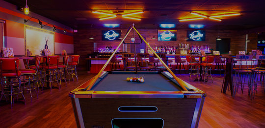 Green billiards table with a bar area behind it
