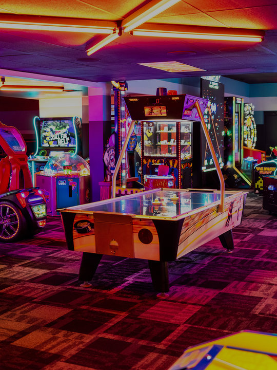 neon lit arcade games and air hockey table