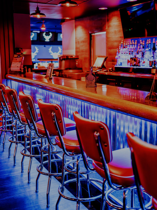 neon lit bar with bar chairs