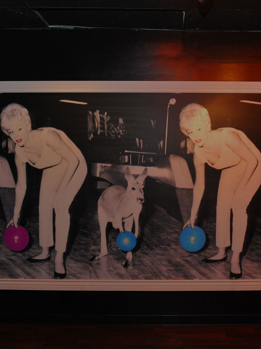 vintage posters on wall of woman and kangaroo holding bowling balls