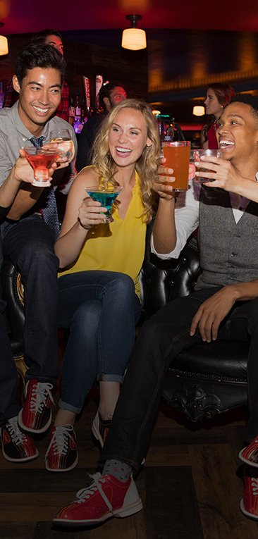 Three people holding up cocktails in celebration