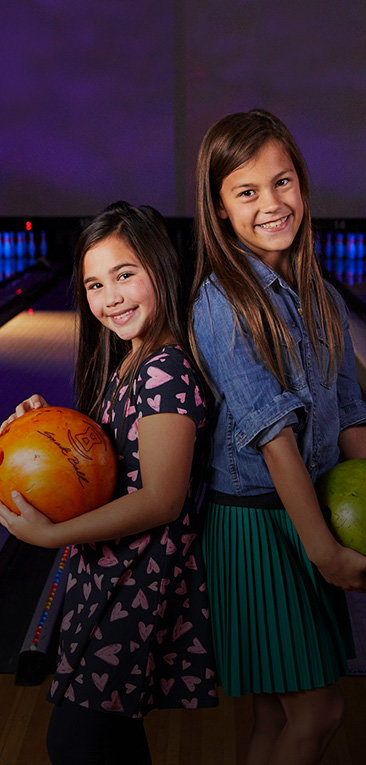 Two girls standing back to back holding bowling balls and smiling