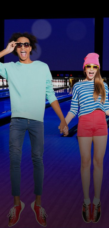 Two teens holding hands and jumping in front of bowling lanes