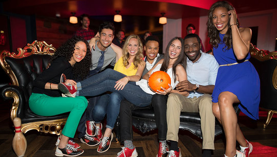 Seven smiling people sitting on a couch and one is holding a bowling ball