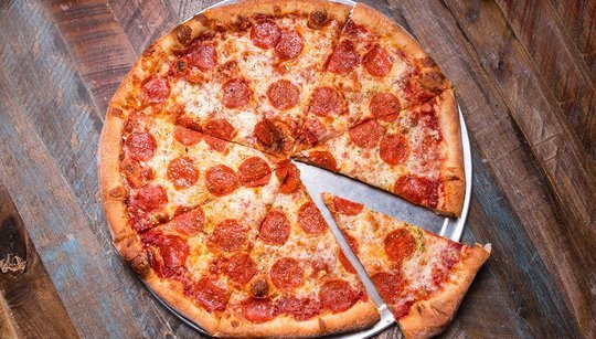 Pepperoni pizza pie on a wood surface