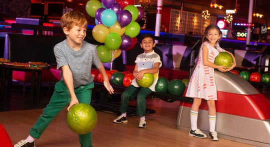 boy bowling with another boy and a girl cheering him on