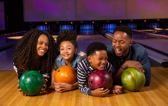 Family laying on floor holding bowling balls and smiling