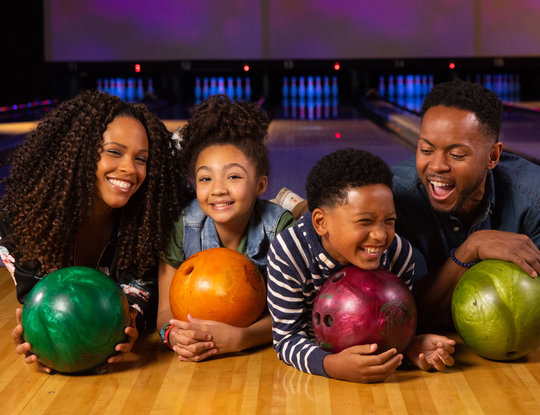 Mom, dad, son, and daughter laying on lanes holding bowling balls