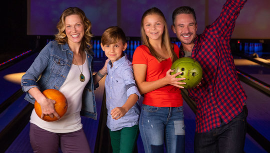 Mom and dad smiling with son and daughter holding bowling balls