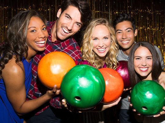 group of people holding bowling balls