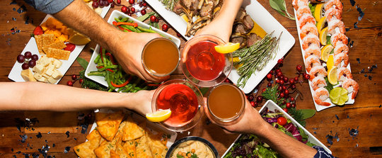 group of 4 people cheering drinks over appetizers