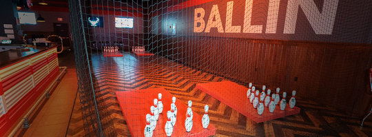 four sets of bowling pins set up on opposite ends of a room