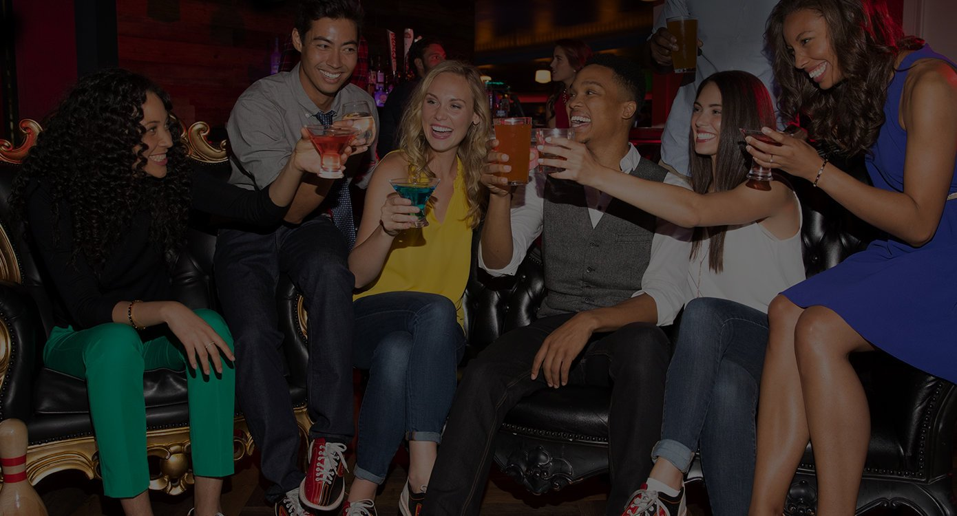 people with drinks sitting and laughing