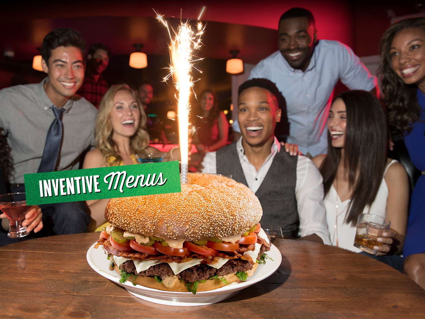 Group of young adults smiling at a large burger with a sparkler. On top is a strip of green foil that reads 'Inventive menus'
