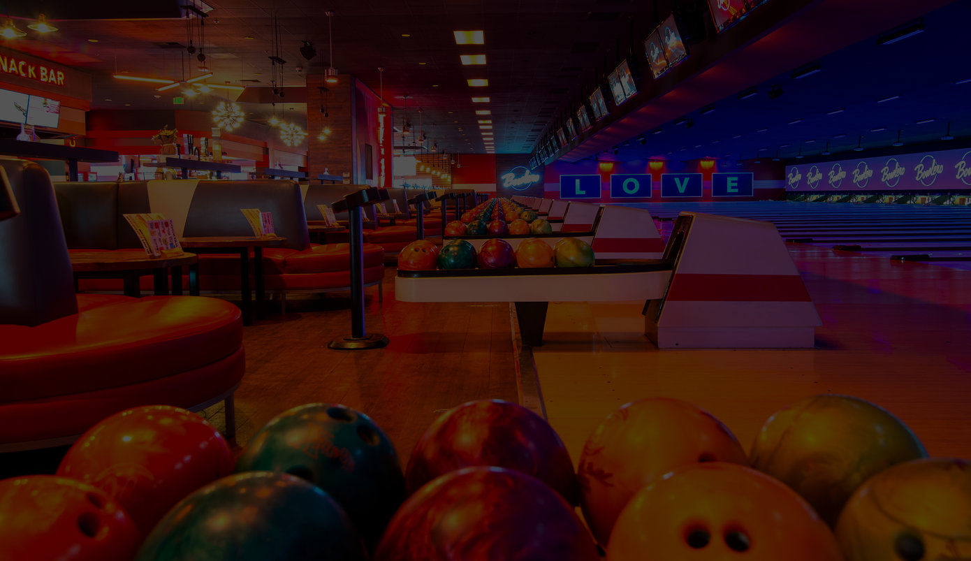 Dark photograph of a bowling alley feature ball returns full of bowling balls