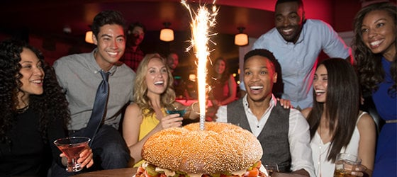 Group of young adults smiling at a large burger with a sparkler