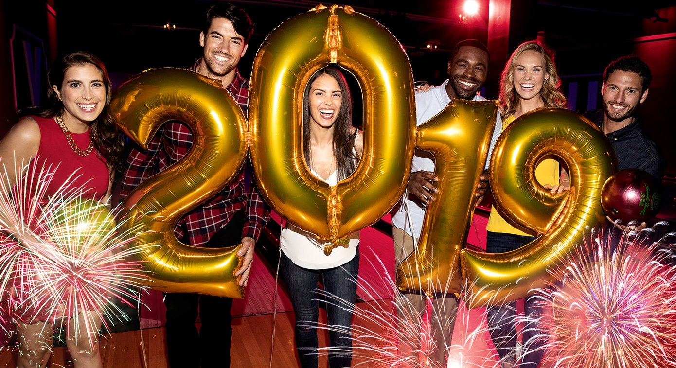 Group of young adults smiling in a bowling alley holding gold balloons that read '2019'