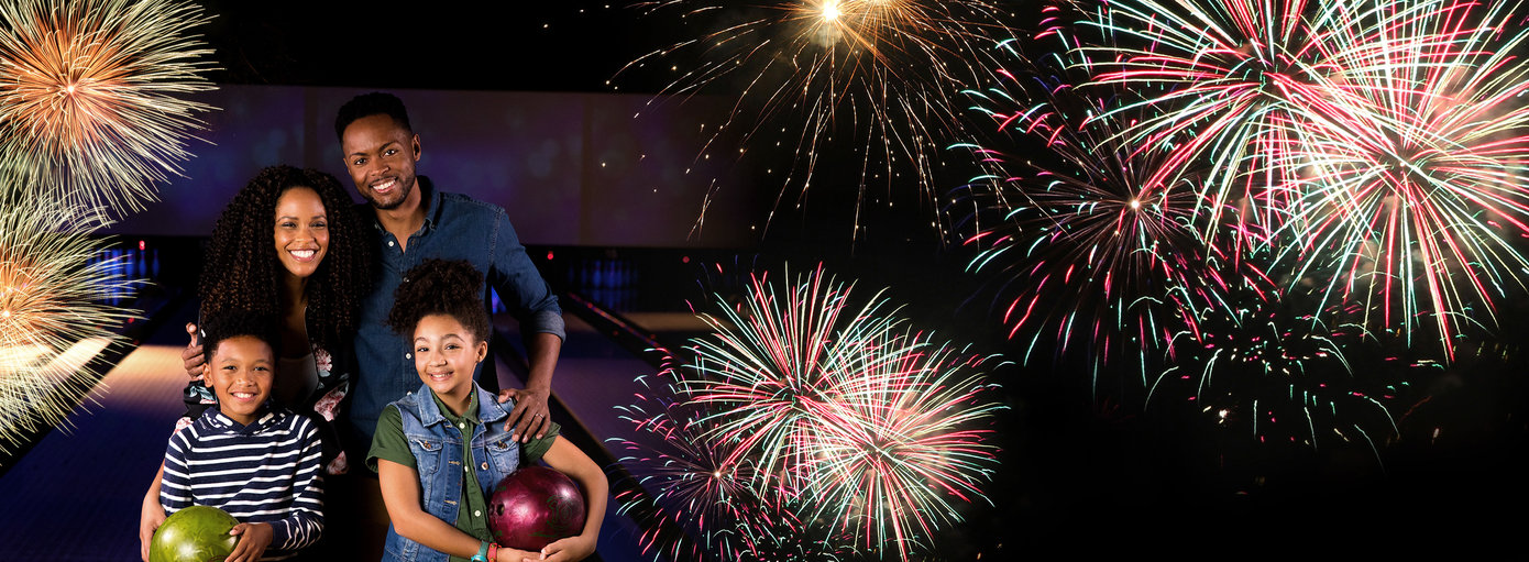 Family holding bowling balls and smiling on the lanes overlayed with fireworks