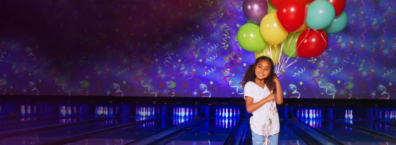 little girl holing balloons in front of a bowling alley