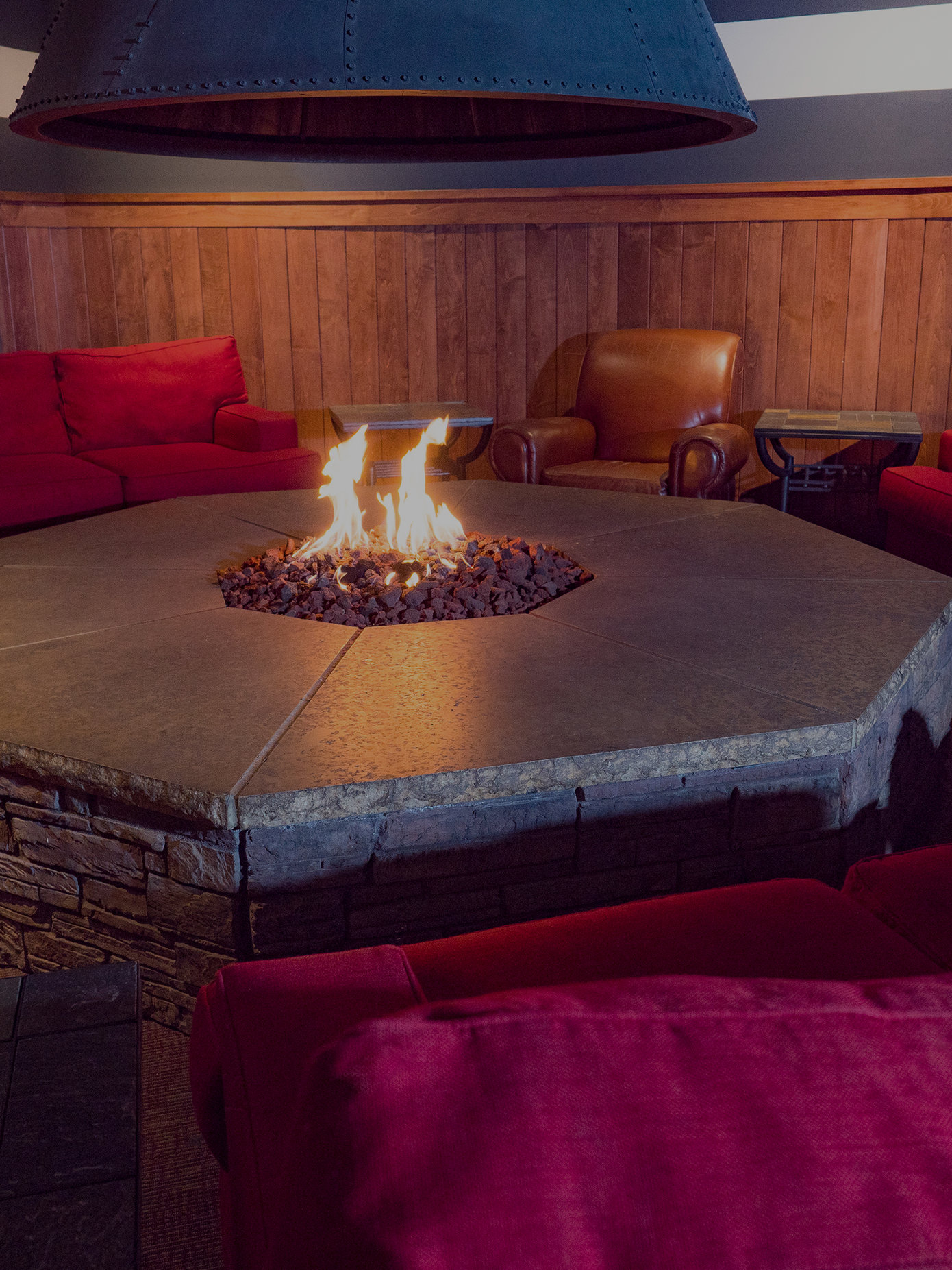 Comfy maroon couches around a fire pit with flames