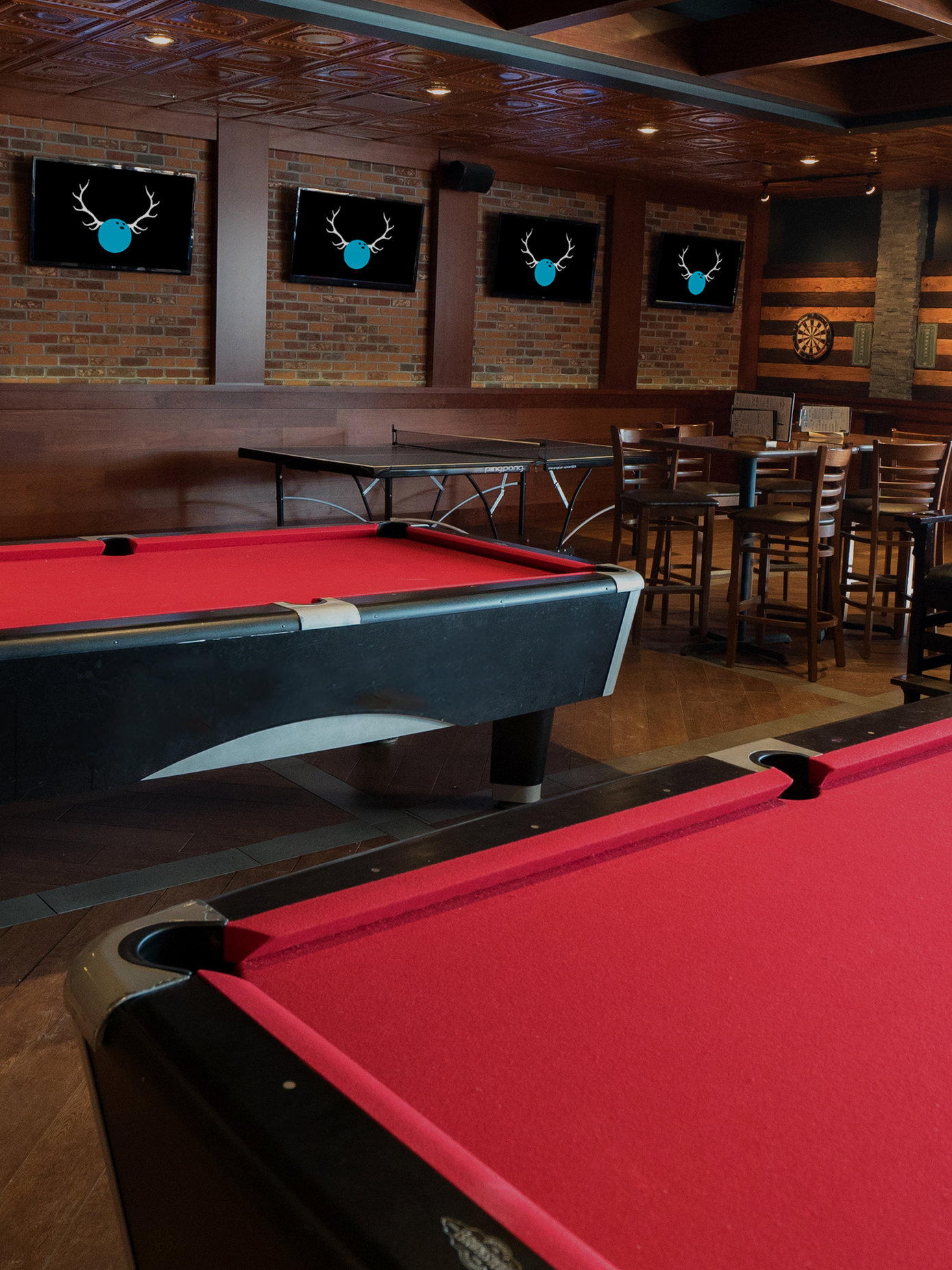Red billiards tables with darts in the background