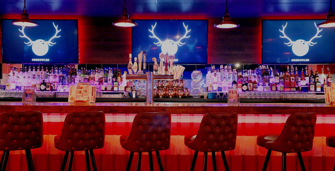 view of neon lit bar with tv screens