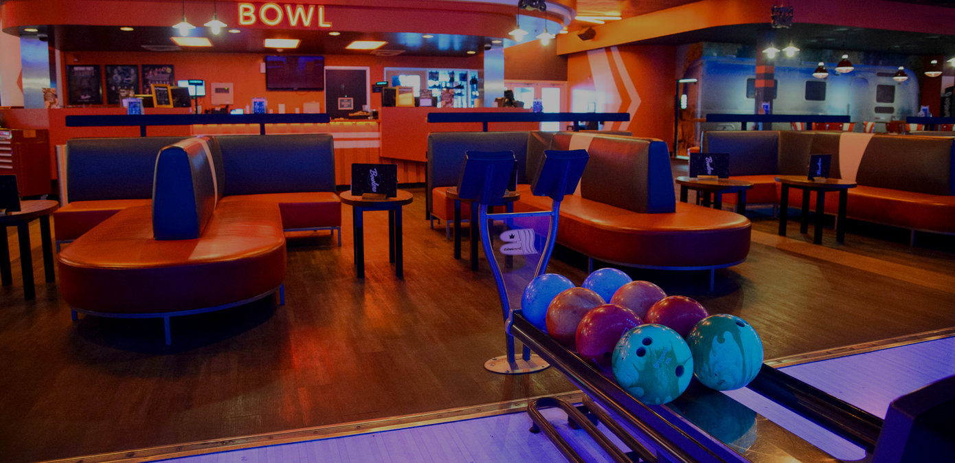 Ball return with bowling balls and a lounge seating area