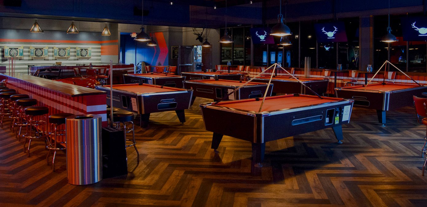 Multiple red billiards tables with darts in the background