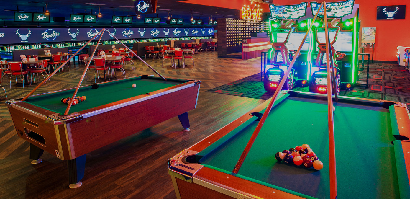 Green billiards table with seating area and lanes in the background