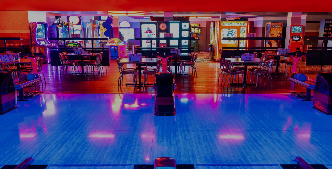 view of bowling ball racks, tables, and a neon lit arcade area