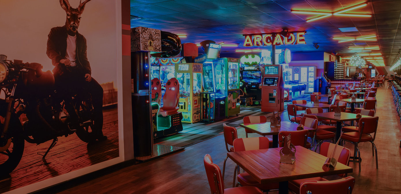 Arcade area with dining tables and a big mural on wall of an anthropomorphic elk on a motorcycle.