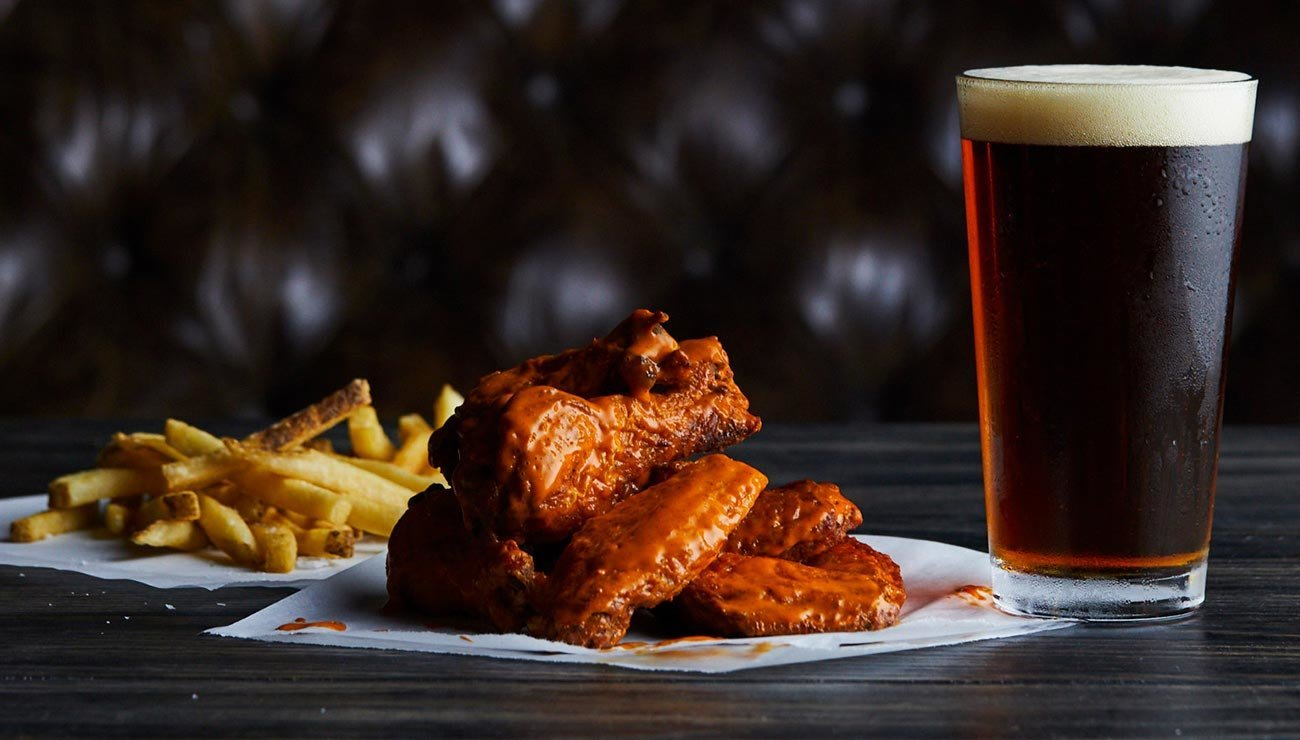 Image of fries, buffalo wings and a beer