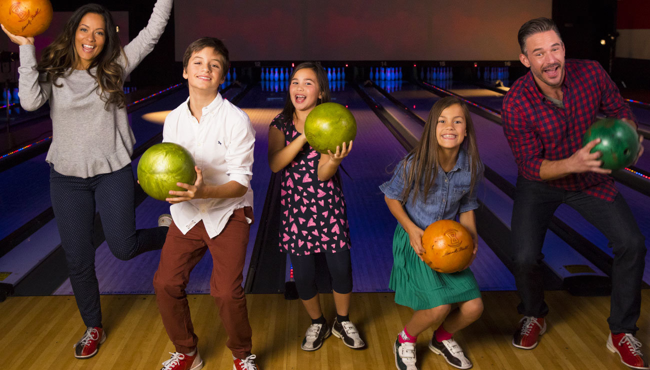 Family holding bowling balls