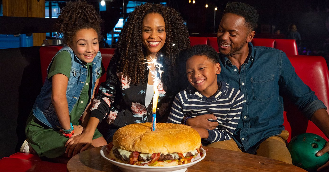 family enjoying a behemoth burger with sparklers