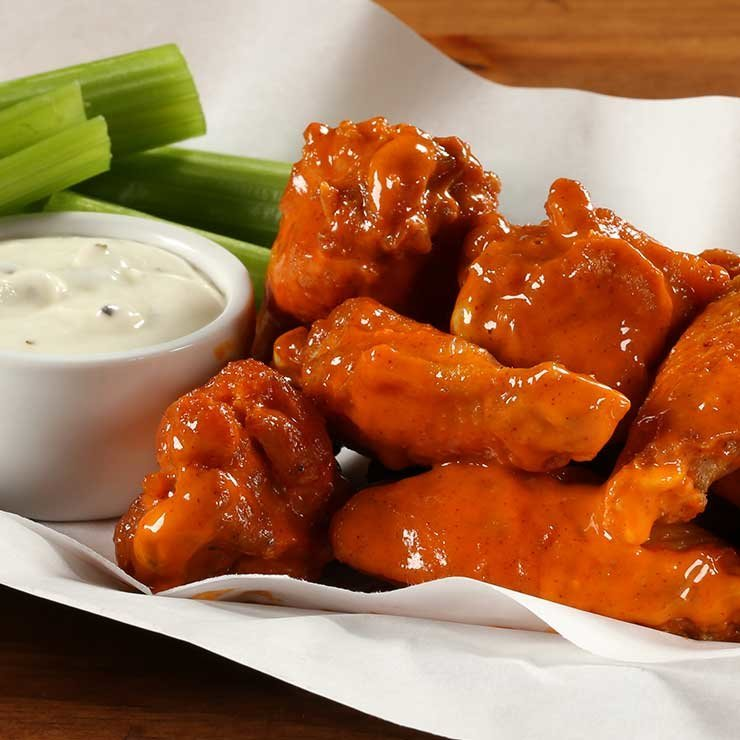 A pile of buffalo wings with ranch dressing and celery sticks on the side