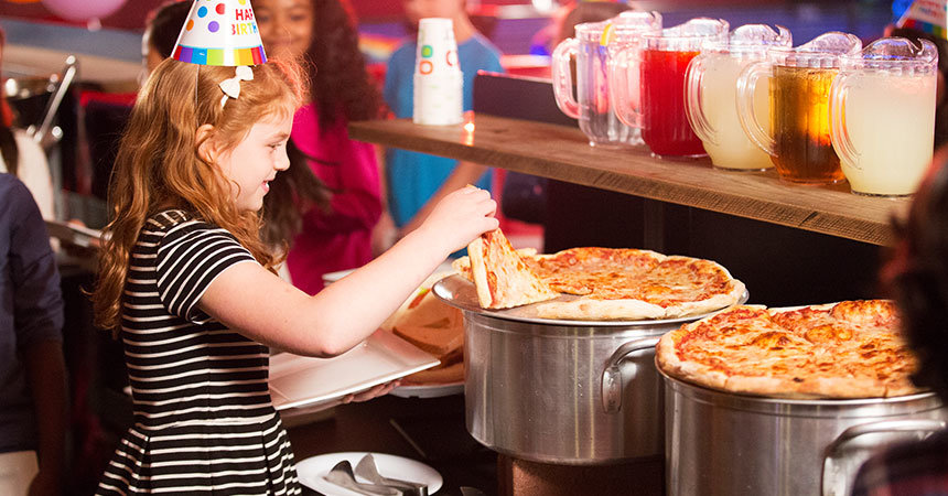 Birthday guest picking up a slice of pizza from a buffet area