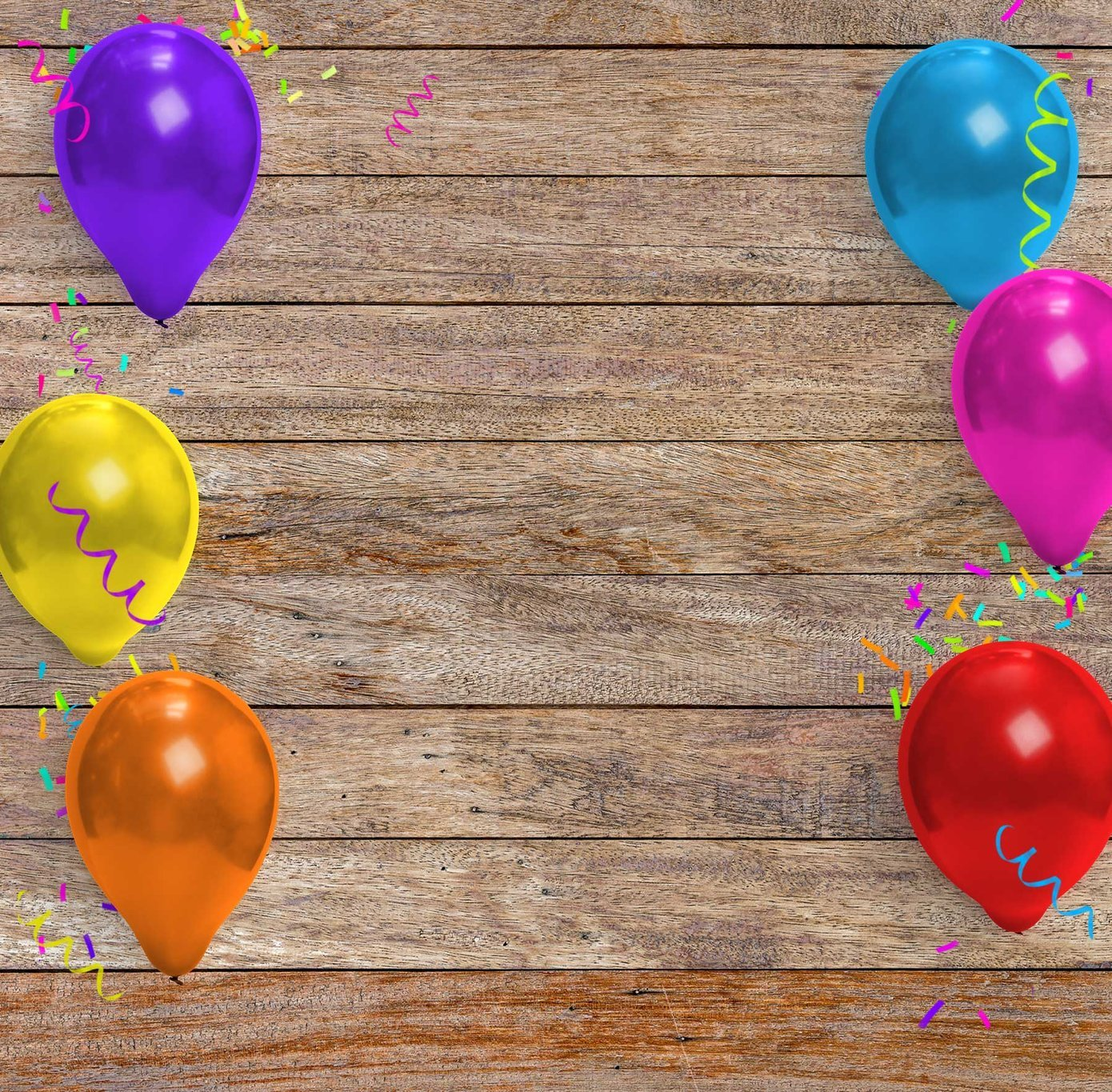Balloons and confetti on a wood background
