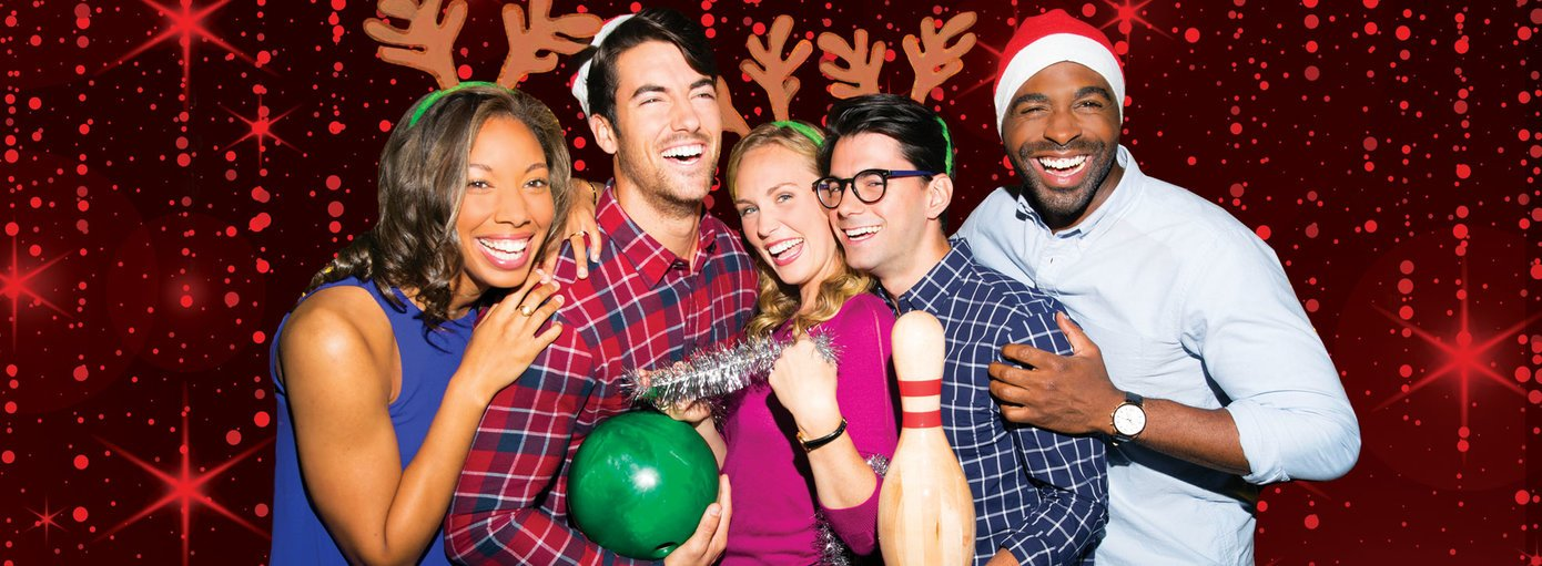 5 friends wearing Santa hats and reindeer ears posing with bowling balls and pins